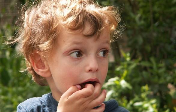 Criança com dedo na boca