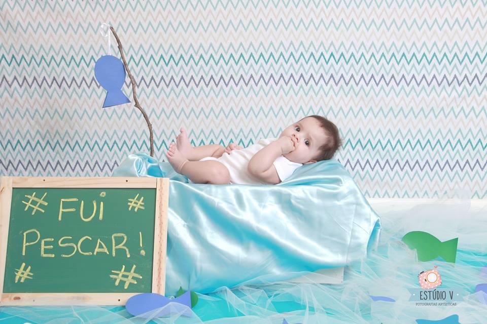 Ensaio fotográfico para bebê com cenário de praia e pescari